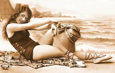 arcade-card-unknown-publisher-woman-sitting-on-beach-set-with-arms-gracefully-over-knees-and-holding-hat-1920s